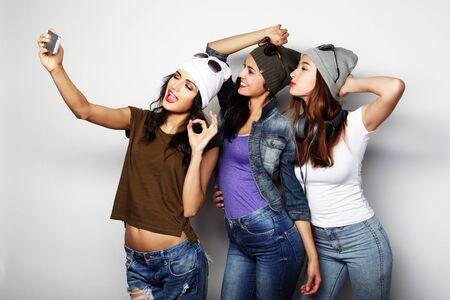 vriendschap, mensen en technologie concept - drie gelukkige tieners met smartphone nemen selfie