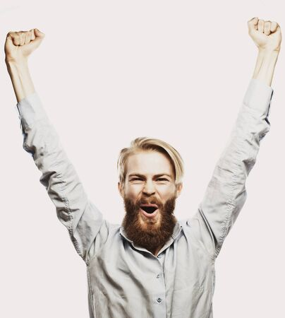 life style, happiness and people concept: young positivity  bearded man showing hand up standing against grey background.