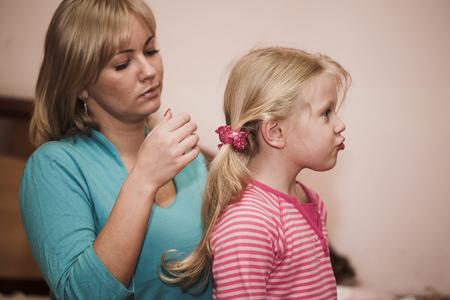 mum and daughter: Mum combs to a daughter hair Stock Photo