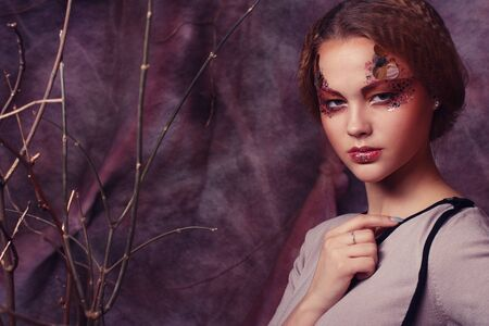 color model: Young woman with bright make up with dry branches