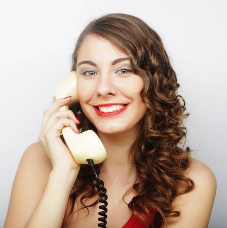 wondered: Amazed beautiful curly woman  talking on white vintage telephone isolated over white background