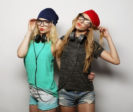 going crazy: Studio lifestyle portrait of two best friends hipster girls wearing stylish bright outfits, hats, denim shorts and glasses, going crazy and having great time together. Stock Photo