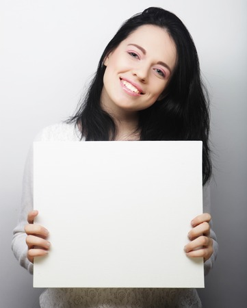 white poster: Smiling young casual style woman showing blank signboard, over grey background isolated