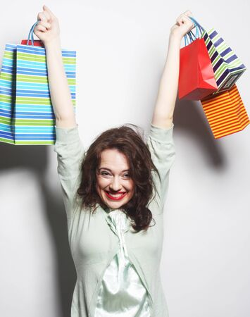 Portrait of a beautiful woman with colored shopping bags