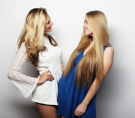 glamour hair: fashion concept: two sexy young women in summer fashion dress