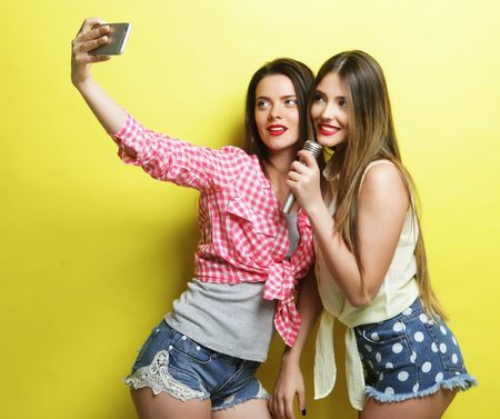 life style, happiness, emotional and people concept: two beauty hipster girls with a microphone  take selfie over yellow background