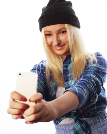 tehnology: People, lifestyle and tehnology concept: pretty teen girl wearing hat, taking selfies with her smart phone - isolated on white Stock Photo