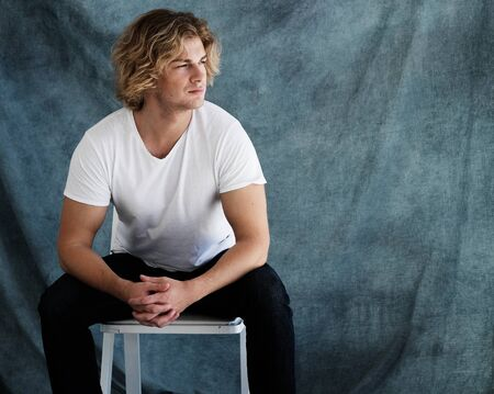 enticement: Fashion portrait of young man in white shirt poses in studio over blue background