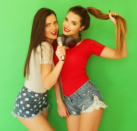 Two young girl friends standing together and having fun over green background