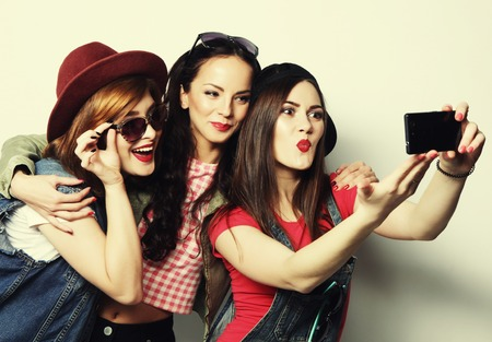 Three stylish sexy hipster girls best friends taking selfie with mobile phone 写真素材