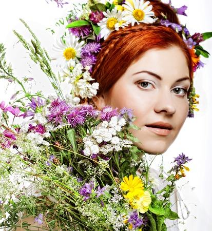 gracefully: model with large hairstyle and flowers in her hair and with bouquet flowers.