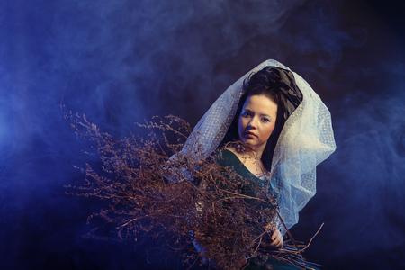 vestido medieval: girl in medieval dress  with bunch of sticks in smoke