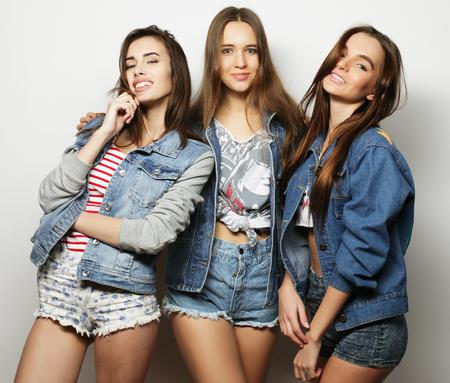 Three stylish sexy hipster girls best friends. Over white background.