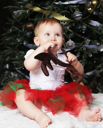 baby near christmas tree: Little baby girl with the gift box near Decorating Christmas tree.