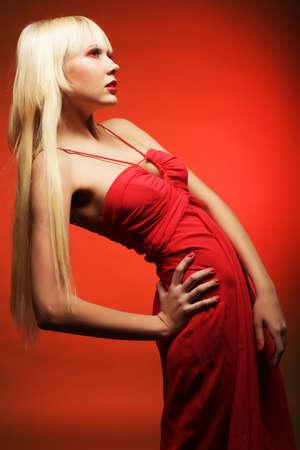 maquillaje de fantasia: Modelo rubio perfecta en el vestido rojo sobre fondo rojo. Maquillaje de fantas�a. Foto de archivo