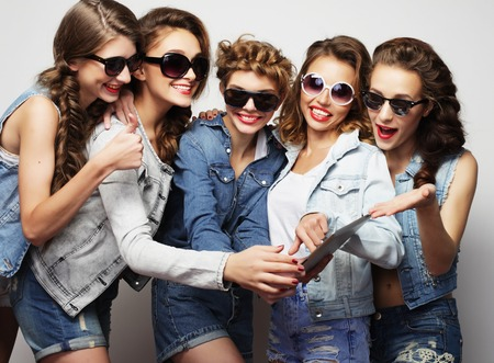 tehnology: life style, tehnology and people concept: five hipster girls friends taking selfie with digital tablet