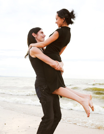 An attractive couple fooling around on the beach Stock Photo