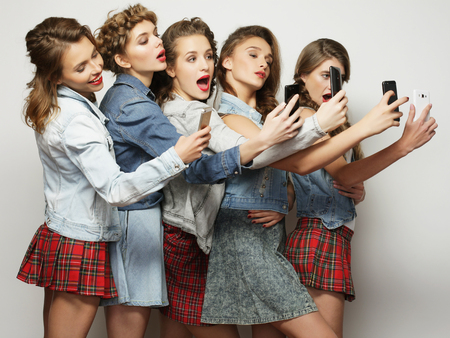 lifestyle, technology and internet concept:group of young women looking at their smartphones