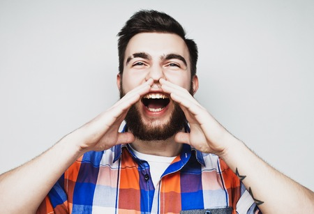 man yelling: life style and people concept: Portrait of a handsome young man yelling, over a gray background