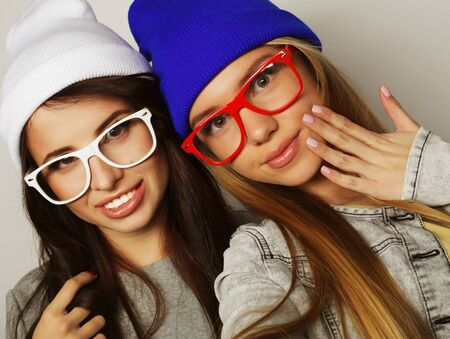 Two teenage girls friends in hipster outfit make selfie over white background Stock Photo
