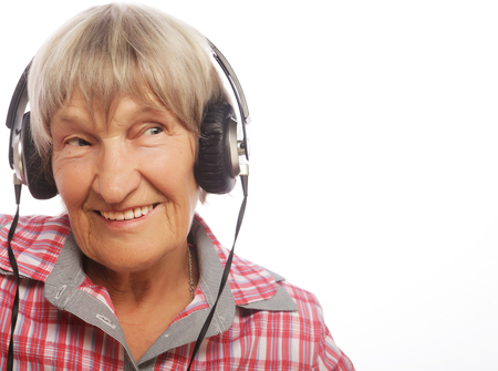 Funny old lady listening music. Isolated on white.