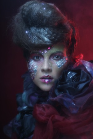the enchantress: Portrait of young stylisn woman with creative visage over red background.