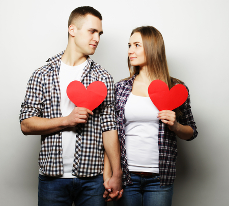 Love, family and people concept: Happy couple in love holding red heart. Stock Photo