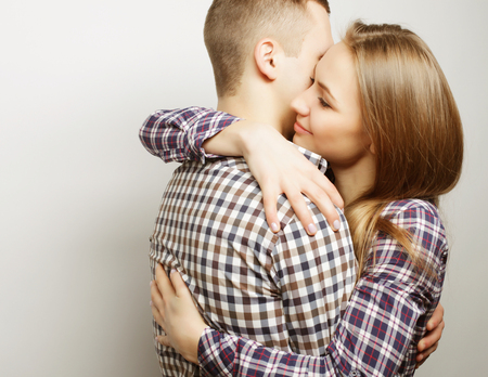 personas abrazadas: El amor, la familia y las personas concepto: hermosa pareja abrazándose feliz sobre fondo gris.