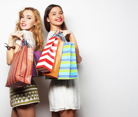 Gorgeous girlfriends with paperbags looking at camera over white background