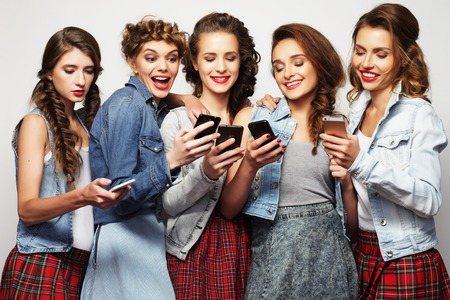 lifestyle, technology and internet concept:group of young women looking at their smartphones photo