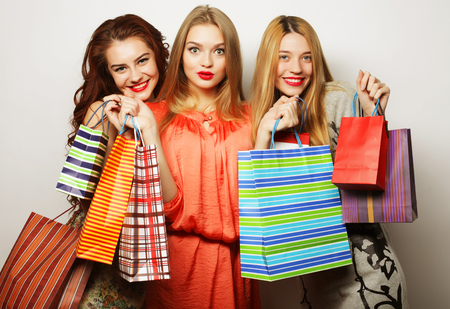 3 persons only: Portrait of young happy smiling women with shopping bags over white background