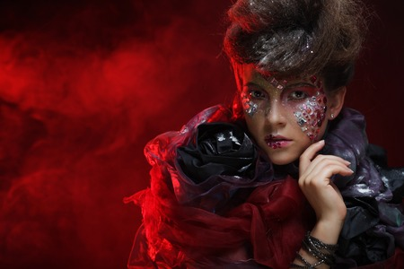loathsome: Portrait of young stylisn woman with creative visage over red background.