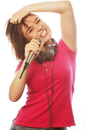 girl  with a microphone singing and having fun, isolated on white