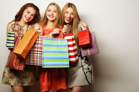 three persons only: Portrait of young happy smiling women with shopping bags over white background