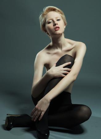 hosiery: Beautiful, seductive woman sitting in fashion pose wearing black pantyhose