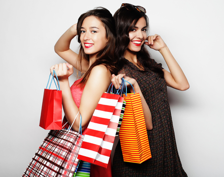 life style, happiness, emotional and people concept: Beautiful  teen girls carrying shopping bags, over white background