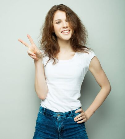 lovely young woman showing victory or peace sign