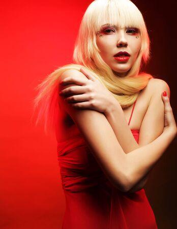 maquillaje fantasia: Modelo rubio perfecta en el vestido rojo sobre fondo rojo. Maquillaje de fantasía. Foto de archivo