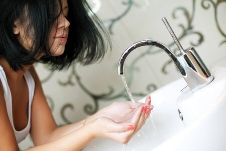 woman washing her hands in the sink