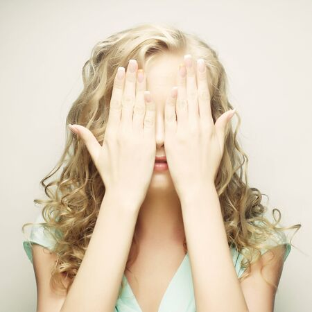 gesticulate: young woman covering her eyes with her hands. Stock Photo
