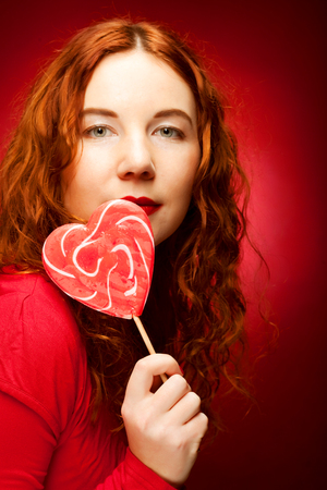 woman with heart caramel over red background