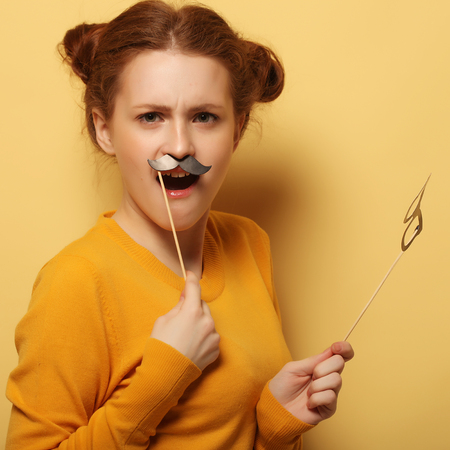 Young woman with  fake mustaches and glasses over yellow backgro Stock Photo