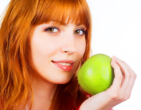 Beautiful young woman holding a green apple Stock Photo