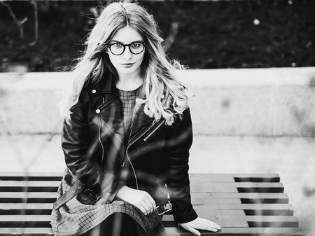 gir: blonde gir sits on a bench, summer city, black and white picture