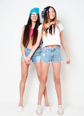 Full body portrait of two hipster girls over white background Reklamní fotografie - 80600379