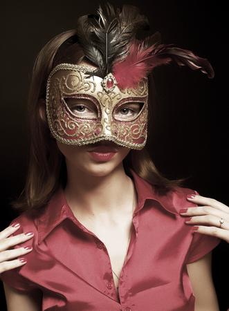 theatre masks: beautiful young woman wearing red cold carnival mask Stock Photo
