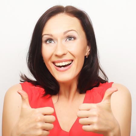 Sourire belle jeune femme montrant thumbs up geste Banque d'images - 82763985