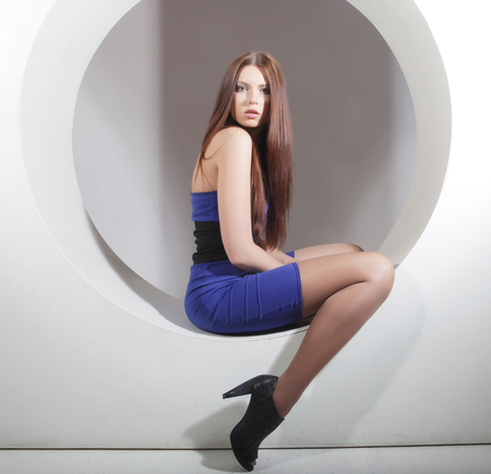 elegance fashion girls look sensuality young: brunette in blue dress sitting in a circle