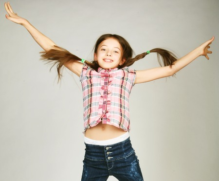 niños actuando: niña salta sobre un fondo gris