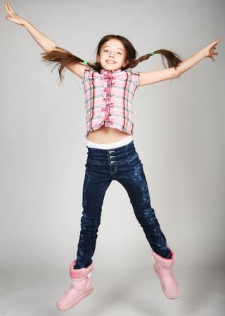 Girl jumps on a gray background Stock Photo